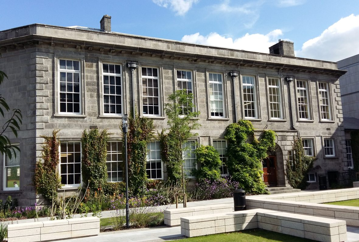 The Botany Department at Trinity College Dublin. The early 20th century building has flower beds in front with climbing plants growing up the walls. There are benches in front of the building.